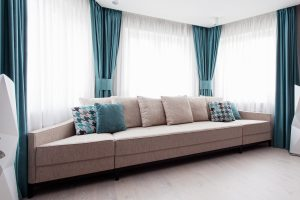 modern couch with pillows matching turquoise draperies