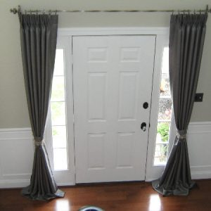 Pinch pleated silk drapes with decorative tie backs framing entryway.
