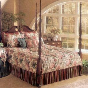 Custom split corner, quilted bed spread with split corners for poster bed. Contrasting pillow shams and throw pillows. Gathered dust ruffle underneath. Custom contrasting table covers on bed side table.