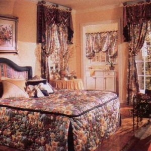 Inverted pleat, quilted pillow wrap bedspread with contrast outline welting around the top. Accent throw pillows and custom headboard. Coordinating balloon shade in bathroom. Swag and Jabot valances with center pelmet over top of Tied Back Pinch Pleated Draperies all done in contrasting fabrics.