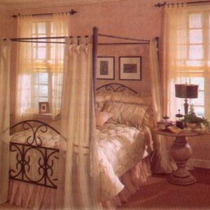 Quilted comforter and pillow shams with decorative throw pillows. Contrasting slightly puddle dust ruffle – sheer tab top drapery panels on the bed frame and the windows.