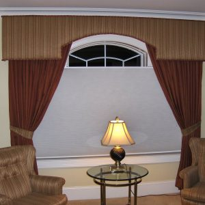 Custom cornice over arch window with tied back drapery panels and contrast reupholstered chairs