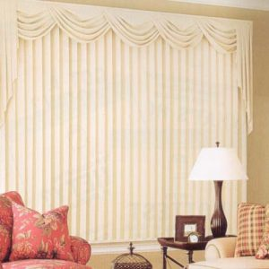 Beautiful wide window dressed with pinch pleated drapery with a swag and jabot valance above.