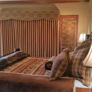 Draperies and cornice covers roman shades over  bedroom window in Chester Springs, PA home.