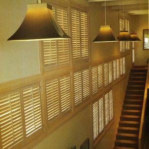 Multi-level wall of stained wooden plantation shutters in a great room ascending the stairway.