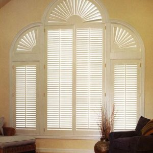 Plantation shutter grouping consisting of various shutter shapes covering an atrium window in the center with a complete arched shutter on the top with single shutter panels on the side windows with half arch shutters on top of them.