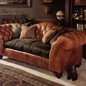 Tufted leather sofa with single velvet covered down seat cushion and accent pillows.