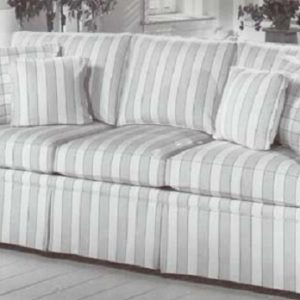 Large skirted sofa in stripe fabric with coordinating block check pillows.