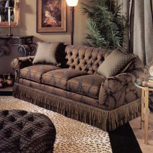 Tufted back three seat sofa with double row large bullion fringe skirt. Tufted ottoman in contrast fabric and trim.