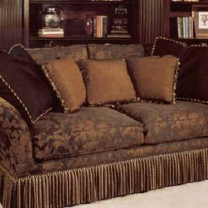 Large love seat with bullion fringe bottom border and accent pillows in contrasting fabrics and trims.