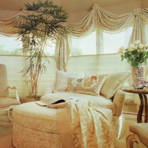 This sun room is decorated with throw swag valances with tassel fringe and rosettes over top of top down bottom up sheer shades. Also showing reupholstered skirted chair and ottoman with coordinating throw pillows and reupholstered arm chairs.