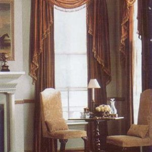 Crown royal wooden molded cornice mounted over a multi fold swag valance with unstructured jabots and decorative trim over a pair of p9inch pleated draperies puddled on the floor. Reupholstered armless occasional chairs with lumbar pillows in coordinating fabrics.