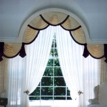 Beautiful arch window treatment featuring swags and jabots with tassel fringe, pinch pleated draperies styled in bishop sleeve, and sheer drapes.