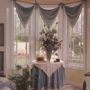 V-point valance in contrast fabrics above coordinating table cover with a v-point table overlay with welting and tassels.