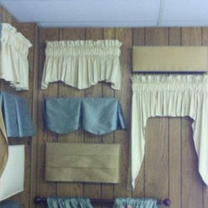 Display of various styles of valances, including rod pocket valances and others.